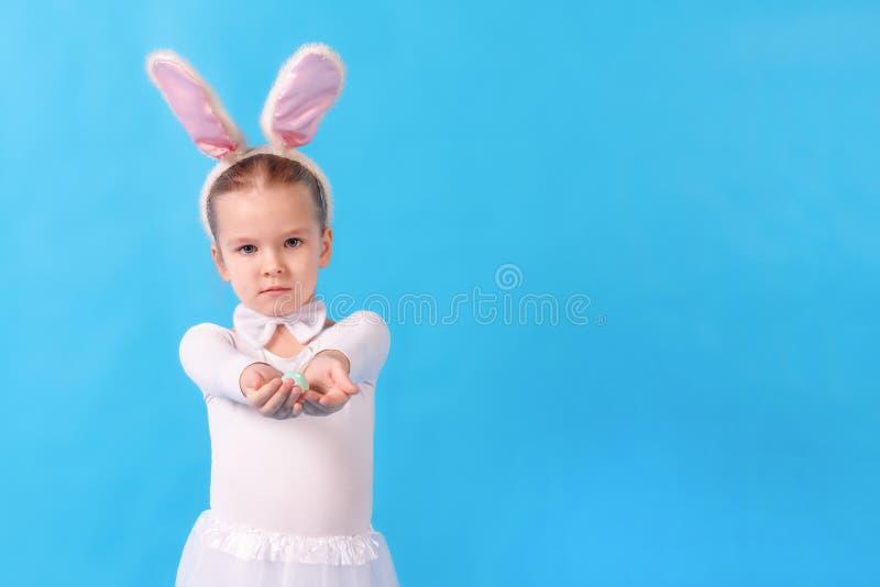 Een kind die een wit konijn dragen Een klein meisje rekt een paasei in haar handen uit Leuk konijntje, vakantiesymbool helder royalty-vrije stock foto