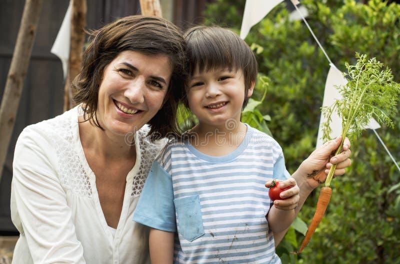 Een kind in een tuin met wortel stock foto's