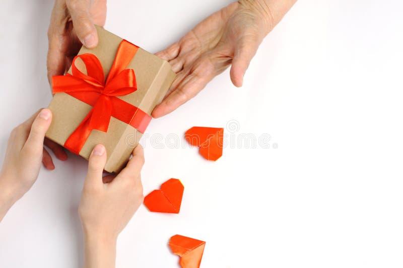 Een kind geeft een gift aan een grootmoeder met liefde stock foto's