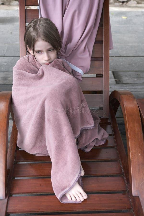 Een kind in een handdoek wordt verpakt zit op een houten stoel die stock afbeeldingen