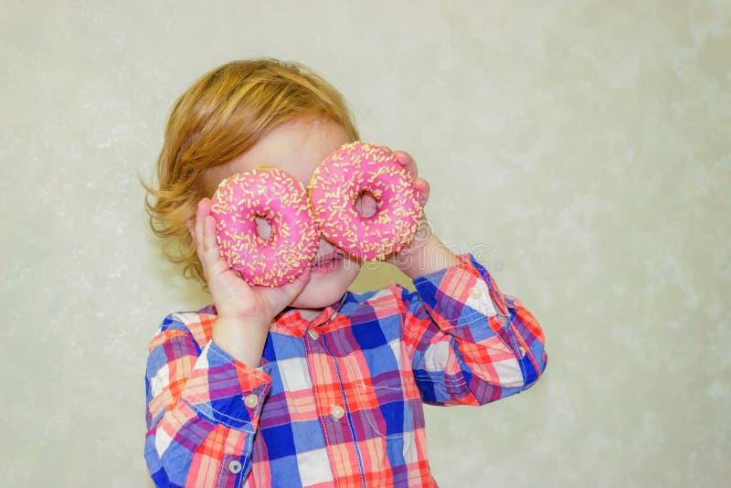 Een kind houdt donuts dichtbij zijn ogen en kijkt door de gaten als door glazen stock fotografie