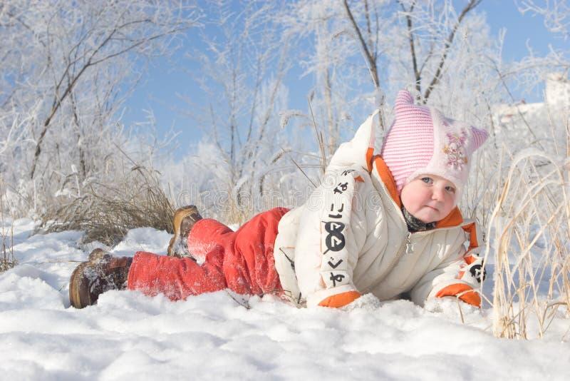 Een kind legt op de sneeuw stock fotografie