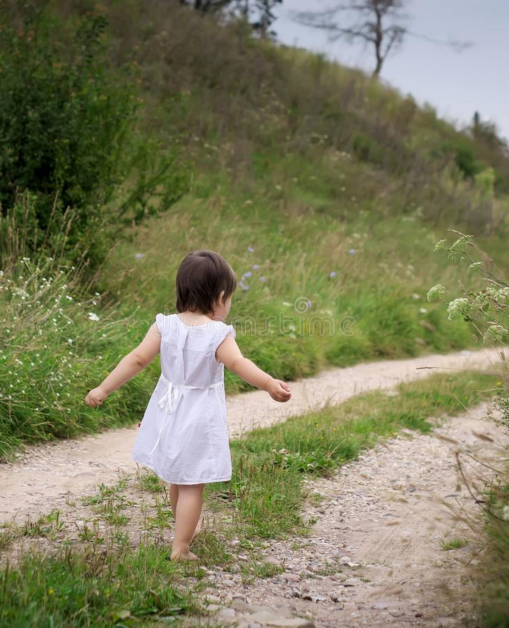 Een kind loopt blootvoets op de zandige weg royalty-vrije stock afbeelding