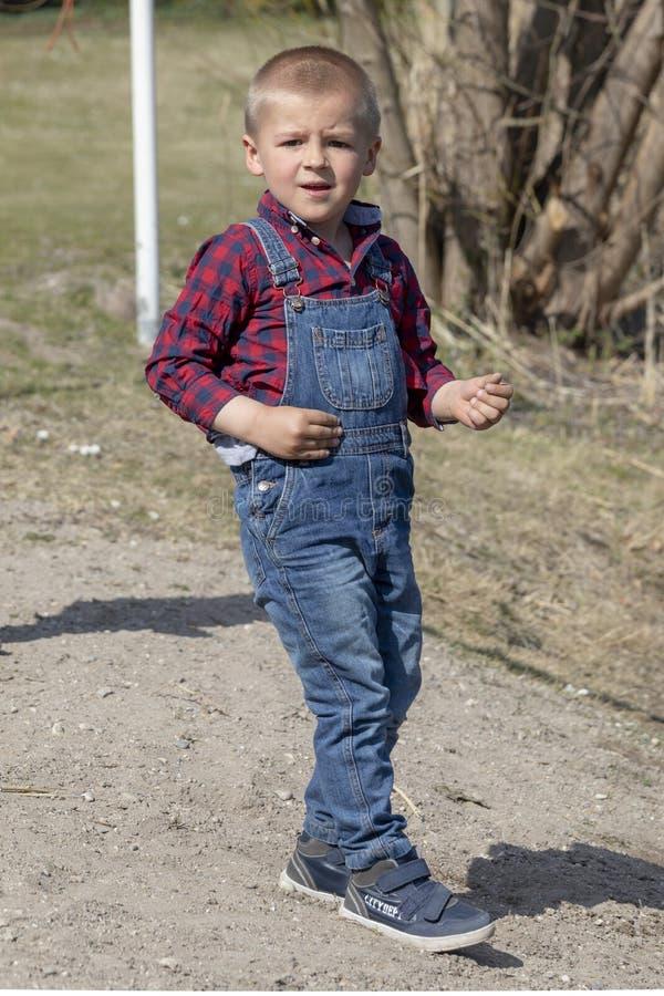 Een kind loopt globaal in het park, een denim Het gelijk maken van zonnig park Groene gras en bomen stock afbeelding
