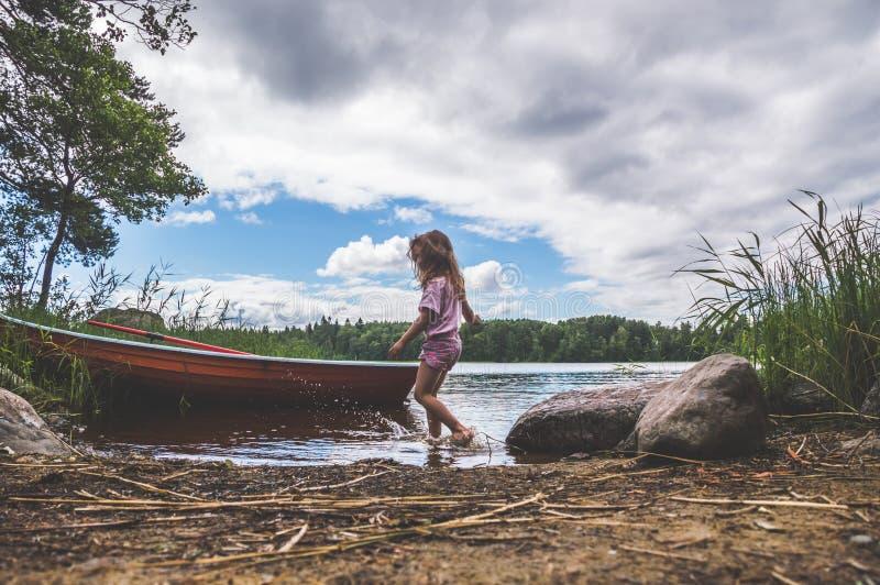 Een kind loopt op het water, meer, rivier, dichtbij de boot in w stock foto