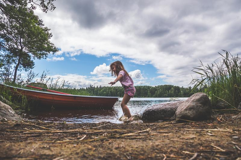 Een kind loopt op het water, meer, rivier, dichtbij de boot in w stock afbeelding