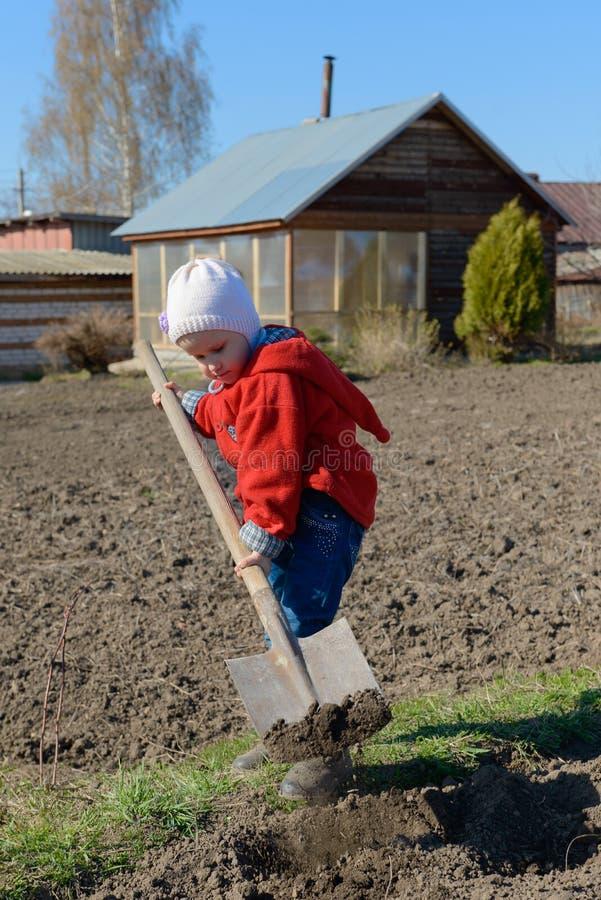 Een kind met een schop graaft de grond royalty-vrije stock afbeeldingen