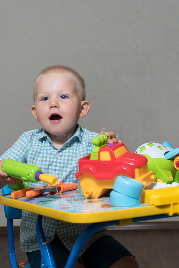 Een kind met stuk speelgoed buigtang en van boorreparaties auto's royalty-vrije stock afbeeldingen
