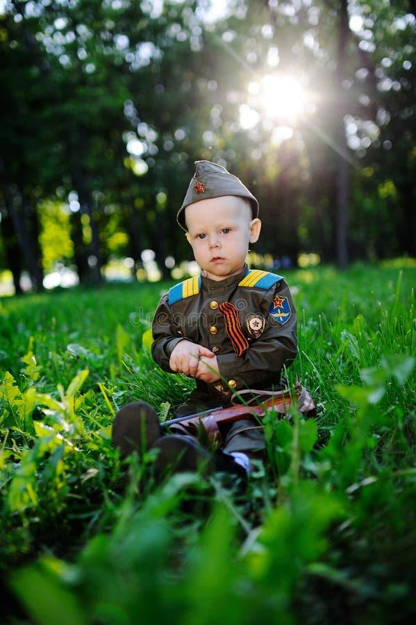 Een kind in militaire eenvormig zit in het gras stock foto's