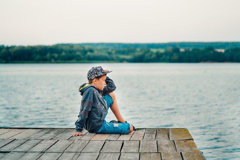 Een kind in modieuze kleren stelt op een fotozitting over de brug op de achtergrond van het meer stock foto