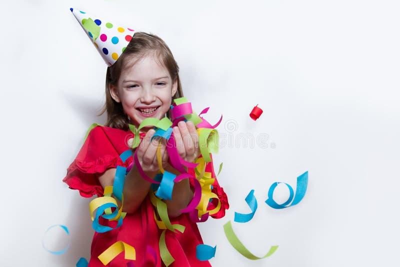 Een kind op een witte achtergrond viert een heldere gebeurtenis, draagt een rode kleding en een GLB stock foto's