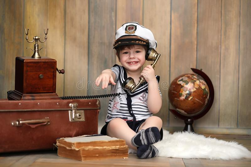 Een kind in een retro binnenlandse en oude telefoon zit op de vloer royalty-vrije stock fotografie