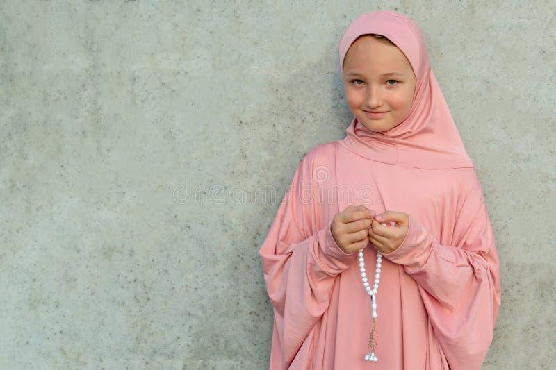 Een kind in een roze hijab met parels in zijn handen met exemplaarruimte Concept van de mensen het godsdienstige levensstijl royalty-vrije stock foto's
