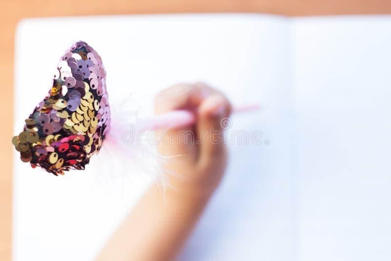 Een kind schrijft in een leeg notitieboekje op een houten bureauachtergrond Terug naar het Concept van de School Hoogste mening stock fotografie