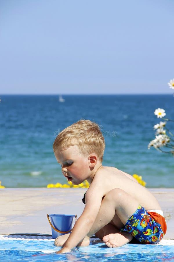 Een kind speelt dichtbij pool Overzees en bloemen bij de achtergrond stock afbeeldingen
