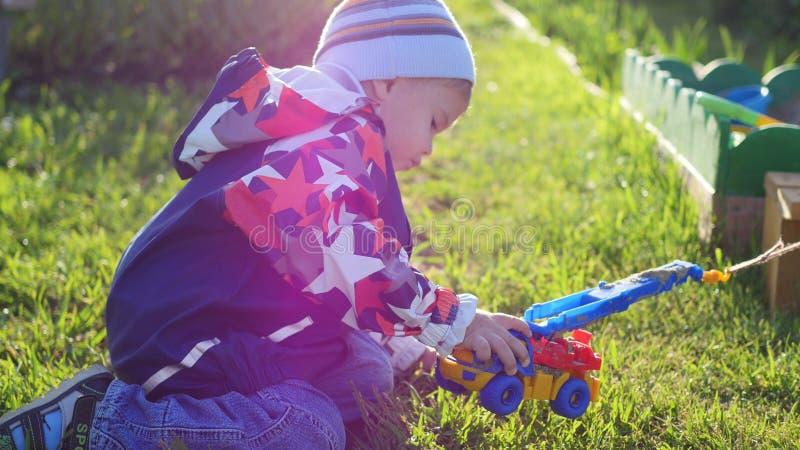 Een kind speelt met een stuk speelgoed auto op het gazon Pret en spelen in openlucht royalty-vrije stock fotografie