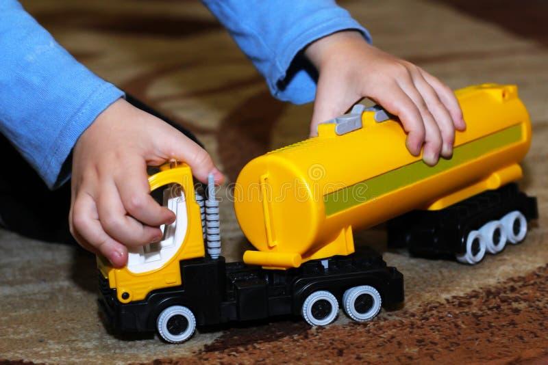 Een kind speelt met een stuk speelgoed vrachtwagen stock afbeelding