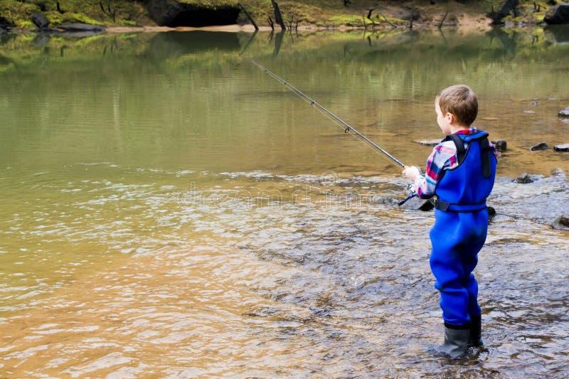Een kind vangt een vis in de rivier stock foto
