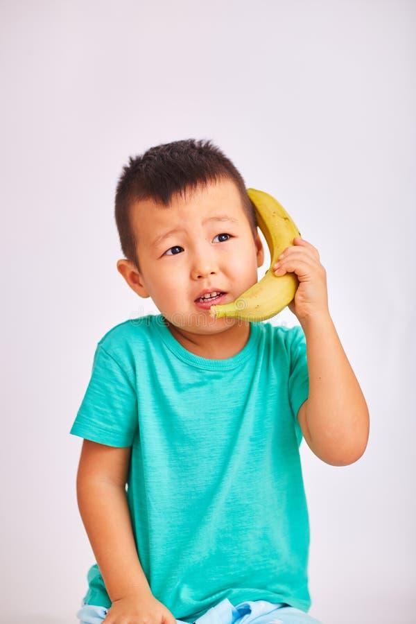 Een kindjongen in een turkoois overhemd, houdt een banaan in plaats van een telefoon terwijl het spreken over een gesprek - vruch royalty-vrije stock afbeelding