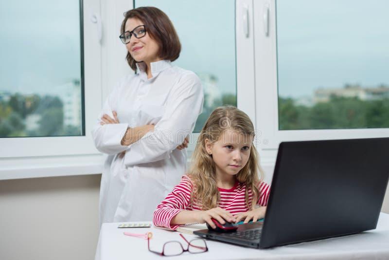 Een kindpatiënt in het artsenbureau zit bij de lijst, bekijkend laptop royalty-vrije stock foto's