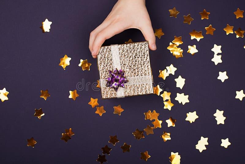 Een kinds hand houdt een gouden giftdoos met een leder-als textuur op een purpere achtergrond met fonkelingen in de vorm van royalty-vrije stock afbeelding