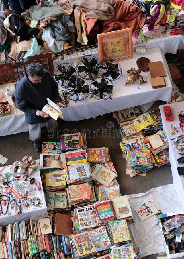 Een klant zoekt koopjes bij de verkoper van de boektribune op een vlooienmarkt stock foto's