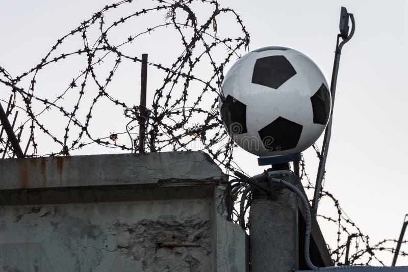 Een klassieke voetbalbal tegen een achtergrond van concrete omheining, prikkeldraad en band met weerhaken Gesloten Russische Voet stock afbeeldingen