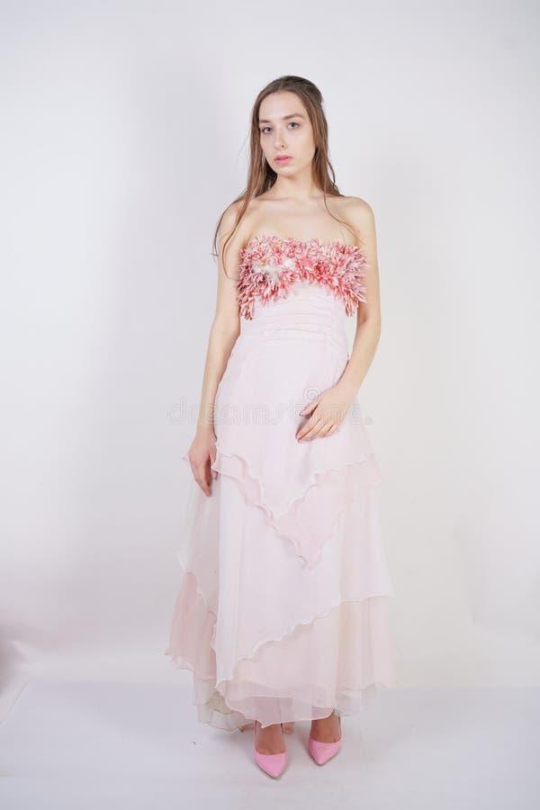 Een kleden de charmante jonge Kaukasische meisjestribunes zich in een lang roze prom met bloembloemblaadjes op haar borst en stel royalty-vrije stock foto