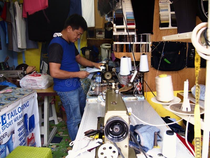 Een kleermaker werkt aan een kleding binnen een het maken winkel stock foto
