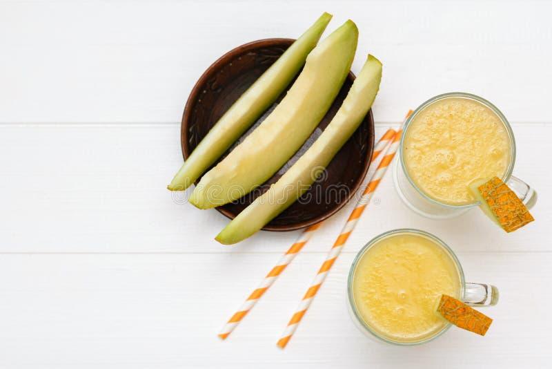 Een kleikom met meloenplakken en twee glasmokken met smoothies op een witte lijst De mening vanaf de bovenkant Vlak leg royalty-vrije stock afbeelding