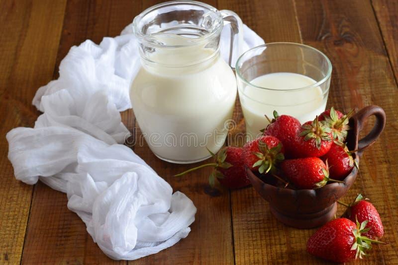 Een kleikop met aardbeien, een karaf melk en een glas melk op de lijst stock afbeelding