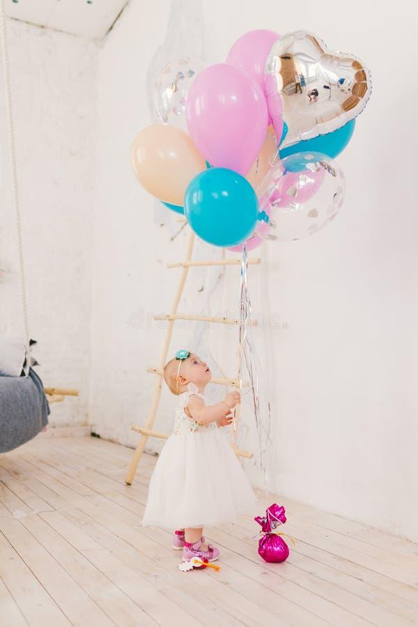Een klein babymeisje in witte overvloedige kleding bevindt zich in woonkamer in het huis dichtbij de decoratieve trap en royalty-vrije stock afbeeldingen