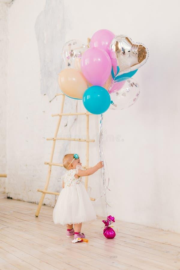 Een klein babymeisje in witte overvloedige kleding bevindt zich in woonkamer in het huis dichtbij de decoratieve trap en royalty-vrije stock fotografie