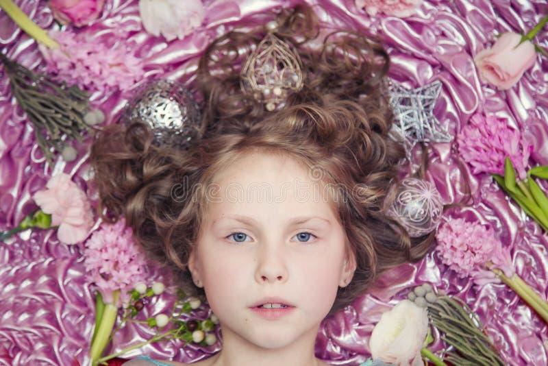 Een klein blond meisje die op een roze zijdestof met een Kerstmisslinger en Kerstmisspeelgoed rond haar hoofd liggen stock afbeelding