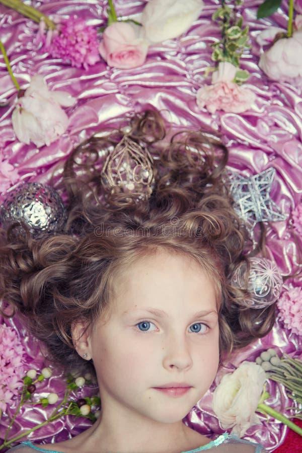 Een klein blond meisje die op een roze zijdestof met een Kerstmisslinger en Kerstmisspeelgoed rond haar hoofd liggen stock foto