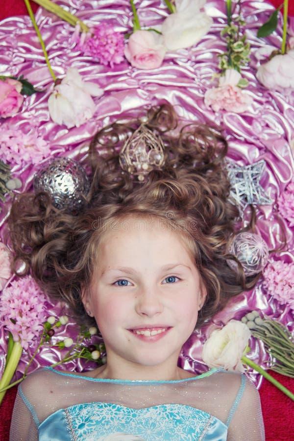 Een klein blond meisje die op een roze zijdestof met een Kerstmisslinger en Kerstmisspeelgoed rond haar hoofd liggen stock afbeeldingen