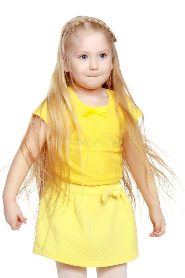 Een klein blonde in een gele t-shirt stock afbeeldingen