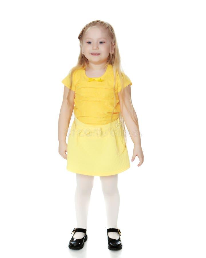 Een klein blonde in een gele t-shirt stock afbeelding