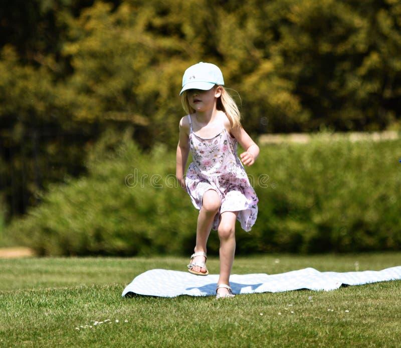 Een klein blondemeisje, ongeveer 4 jaar oud, in een regenbooghonkbal GLB danst in de zonneschijn bij een picknick in een park het stock fotografie