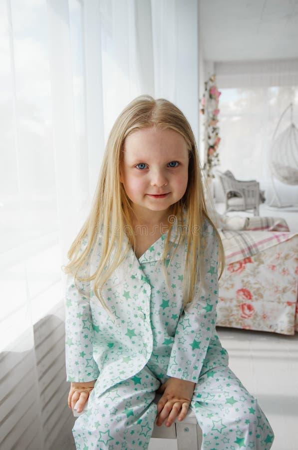 Een klein blondemeisje zit op een stoel door het venster Meisje in pyjama's stock afbeelding