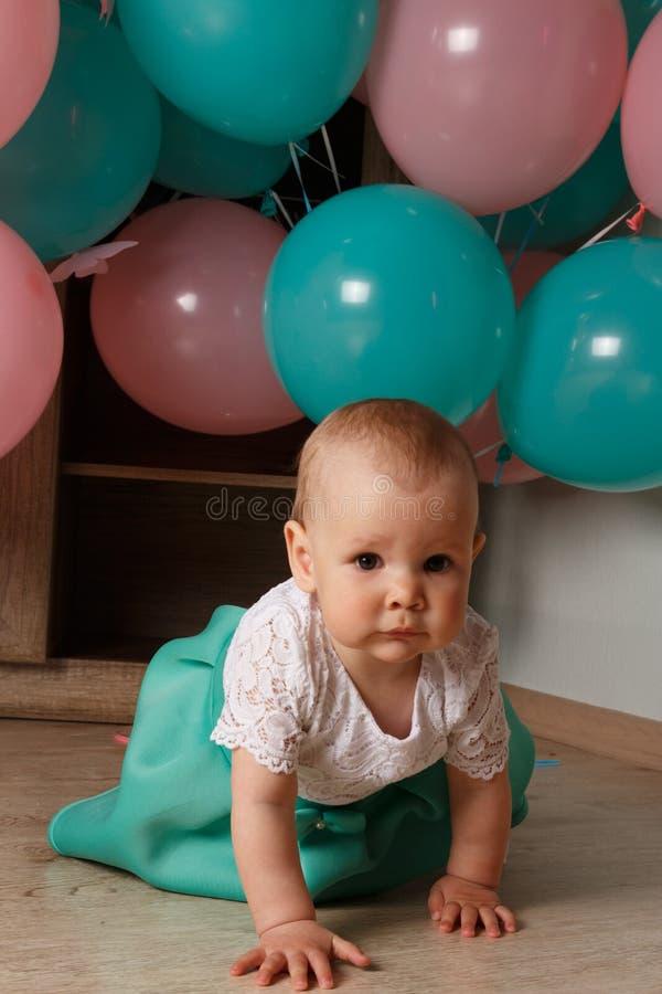 Een klein, charmant kind, een meisje, viert haar eerste verjaardag, zittend naast haar met ballons De Organisatie van de kinderen stock afbeelding