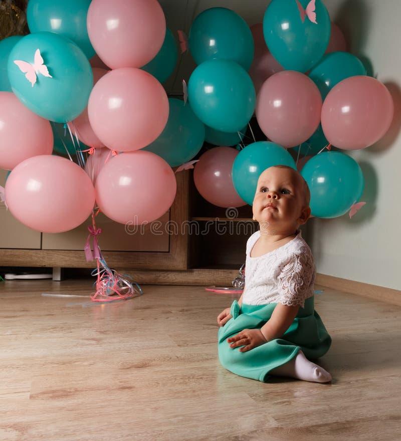 Een klein, charmant kind, een meisje, viert haar eerste verjaardag, zittend naast haar met ballons De Organisatie van de kinderen stock afbeeldingen