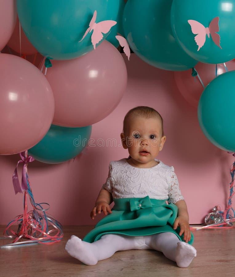 Een klein, charmant kind, een meisje, viert haar eerste verjaardag, zittend naast haar met ballons, op een roze achtergrond Kinde royalty-vrije stock afbeelding