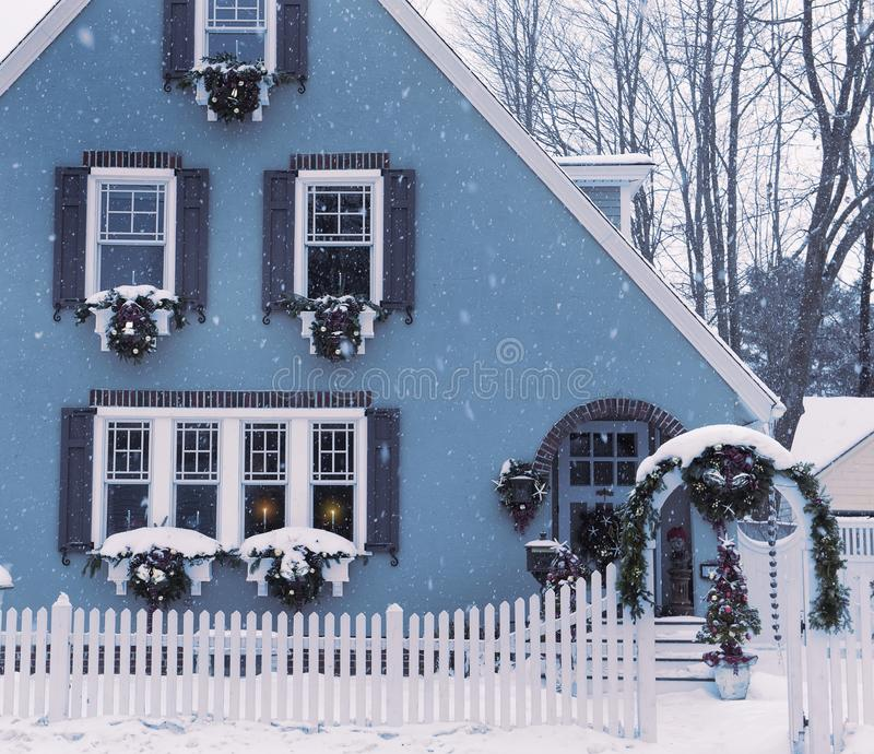 Een klein comfortabel die huis, vensters met Kerstmiskronen wordt verfraaid en kaarsen in de vensters De V.S. maine Traditionele  stock afbeelding