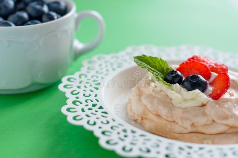 Een klein dessert van schuimgebakjepavlova met aardbei en munt stock foto