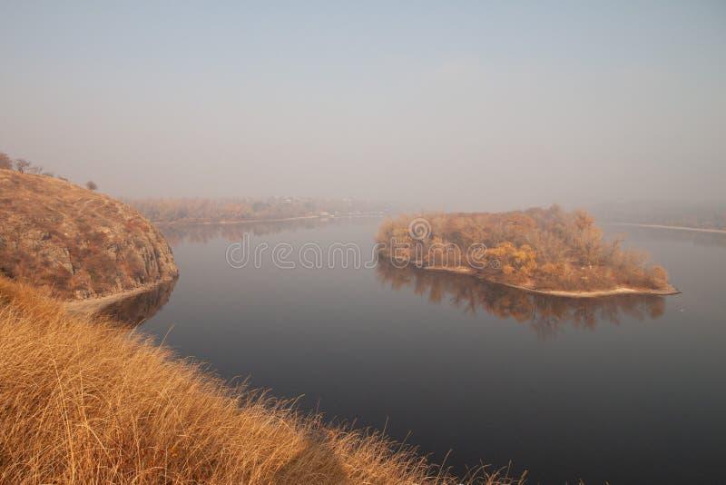 Een klein die eiland alsof drijvend in het midden van een rivier, in ochtendmist wordt gehuld royalty-vrije stock afbeelding
