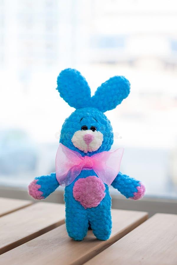 Een klein gebreid blauw konijn met roze bowtie op houten oppervlakte Gebreid met de hand gemaakt stuk speelgoed, Amigurumi stock foto