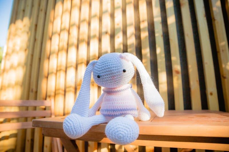 Een klein gebreid wit konijn in een roze kleding op houten lijst Gebreid met de hand gemaakt stuk speelgoed, handwerk Leuk konijn royalty-vrije stock afbeelding