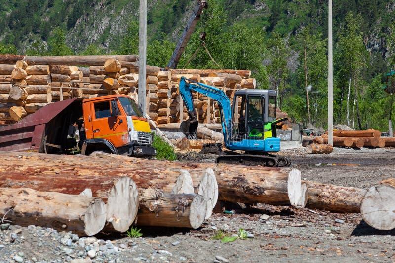 Een klein graafwerktuig en een grote vrachtwagen doen het werk van het laden van en het verwijderen van bouwmaterialen tegen de a royalty-vrije stock foto