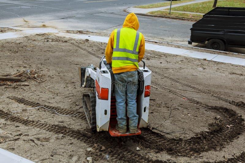 Een klein graafwerktuig werkt aan de straat in de zomer stock fotografie